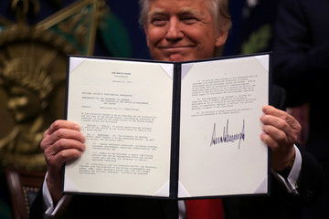 """U.S. President Donald Trump shows an  executive action he said would begin the rebuilding of the U.S. military by """"developing a plan for new planes, new ships, new resources and new tools for our men and women in uniform"""" at the Pentagon"""