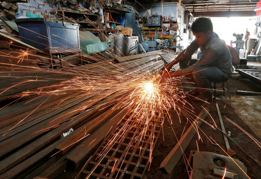 A worker grinds a metal gate inside a household furniture manufacturing factory in Ahmedabad