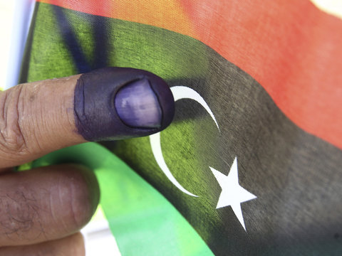 A Libyan man living in Jordan shows his right index finger stained with blue ink after casting his vote at a polling station in Amman