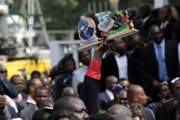 A man holds a handicraft with the picture of Haitian President Moise and a map of Haiti during the speech of Moise at the inauguration in the National Palace of Port-au-Prince