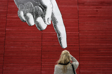 A woman photographs artwork of a large hand on a wall in central London