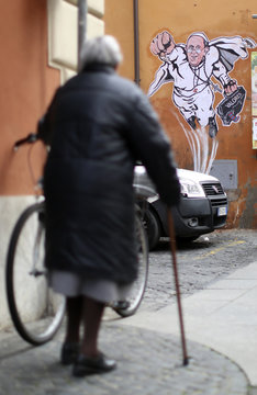 A woman walks by a large drawing of Pope Francis depicting him as a superhero on a wall near the Vatican