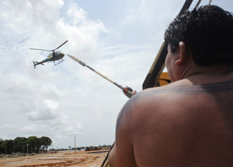 An Amazonian native points an arrow at a police helicopter flying overhead during an occupation of the Belo Monte hydroelectric dam site in protest against the dam's construction near Altamira