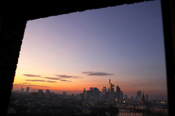 The skyline is seen through a window frame as the sun goes down late in the afternoon in Frankfurt