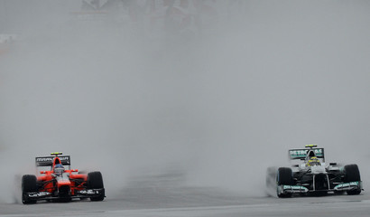 Mercedes driver Rosberg and Marussia driver Pic steer their cars through the rain during a practice session for the German F1 Grand Prix in Hockenheim