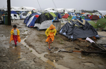 Migrants walk in a mud at a makeshift camp on the Greek-Macedonian border, near the village of Idomeni