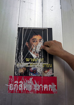 """Volunteers remove stickers depicting Thai Prime Minister Abhisit Vejjajiva and the words """"murderer of people"""", placed on a wall by anti-government 'red shirt' protesters, in Bangkok"""