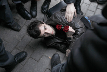 Russian police surround an opposition party supporter while detaining him during a protest rally in central Moscow