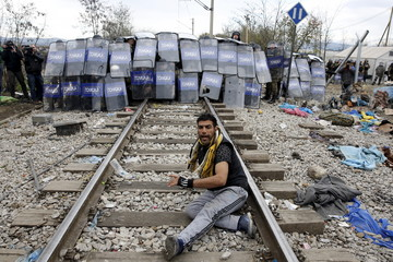 A stranded migrant reacts in front of a Macedonian police cordon as they clash after a migrant was electrocuted and badly burned when he climbed on top of a train wagon, near the village of Idomeni