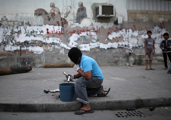 A young anti-government protester collects used tear gas canisters during clashes with riot police in the village of Sharakan, south of Manama