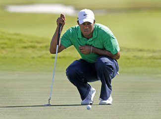 Tiger Woods of the U.S. lines up a putt on the 12th hole during third round play in the WGC-Cadillac Championship