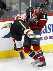 Minnesota Wild defenseman Marek Zidlicky upends Calgary Flames right wing David Moss in St Paul