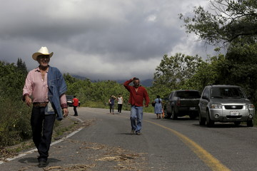 Residents walk down a road, near a bridge damaged by Hurricane Patricia, on the outskirts of the town of Comala, in the Mexican state of Colima