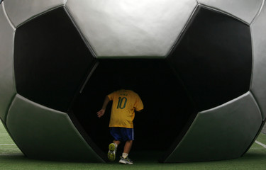 A boy plays in front of a sphere in the shape of a football during a World Cup promotional event outside a shopping mall in Hong Kong