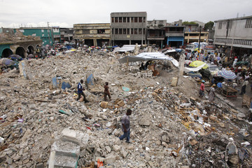 Residents walk over debris of buildings destroyed after an earthquake in downtown Port-au-Prince