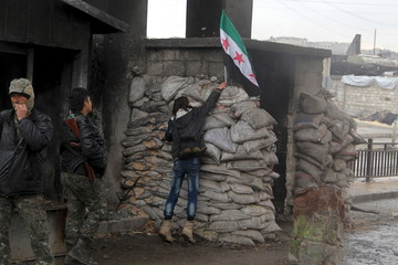 A protester places an opposition flag at a checkpoint controlled by Free Syrian Army fighters, during a protest asking for the release of prisoners held in the government jails in al-Fardous neighbourhood of Aleppo