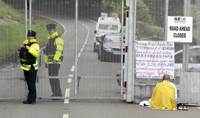 A Buddhist demonstrator protests at the security fence surrounding the G8 Summit at Lough Erne in Enniskillen, Northern Ireland