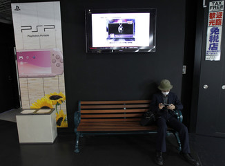 A man uses Sony's portable PlayStation game console at an electronics shop in Tokyo