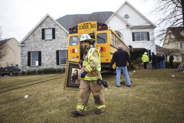 A fire fighter removes a family portrait from a house that was crashed into by a school bus at the Windermere Development in Blue Bell