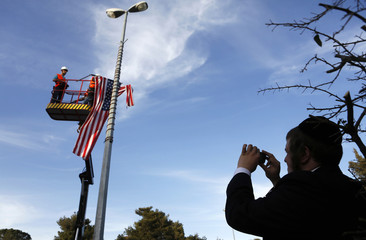 A man takes a photograph of municipality workers as they hang an American flag near Israeli President Peres' residence in Jerusalem, ahead of U.S. President Obama's visit to Israel