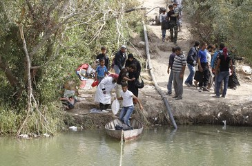Syrians wait to cross to Turkey by boat over the Orontes river on the Turkish-Syrian border near the village of Hacipasa in Hatay province
