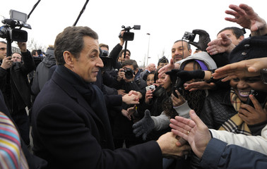 France's President Nicolas Sarkozy shakes hands with people outside the French solar panel maker PhotoWatt in Bourgoin-Jallieu