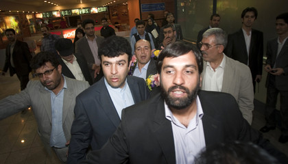 Iranian Ali Vakili Rad's bodyguards guide him after leaving a news conference in Tehran