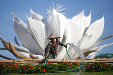 A girl wearing a hat and tanaka paste on her face waters flowers at the one of main intersections of Naypyitaw
