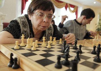 An elderly woman takes part in a chess competition at a gerontological center in Stavropol