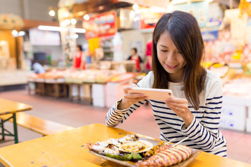Woman taking photo on her dish in wet market of Japan