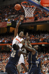 Syracuse Orange center Melo takes shot over Pittsburgh Panthers forwards Zanna and Robinson during first half of their NCAA men's basketball game in Syracuse