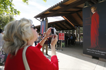 A woman takes a picture of a portrait of  former first lady Nancy Reagan that greets visitors as they arrive to pay their respects at the Ronald Reagan Presidential Library