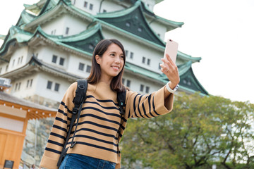 Woman travel in Nagoya castle and taking selfie
