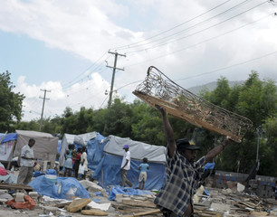 A man who was evicted from his tent encampment, carries a wooden bed frame in Port-au-Prince