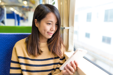 Young Woman working on mobile phone on train