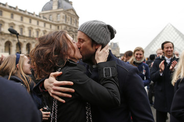 A couple share a kiss during a kissing flashmob event to celebrate Valentine's Day in front the the Louvre Museum in Paris