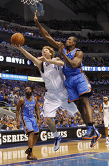 Dallas Mavericks' Nowitzki goes up for the shot as he is defended by Oklahoma City Thunder Ibaka during their NBA Western Conference quarter-final playoff basketball game in Dallas