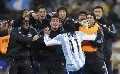 Argentina's Tevez celebrates his second goal with his coaching staff during the 2010 World Cup second round soccer match against Mexico in Johannesburg