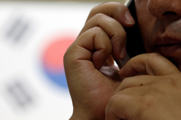 A North Korean defector, who declined to be named and requested his face not to be photographed due to his safety, talks on his phone during an interview with Reuters in Seoul