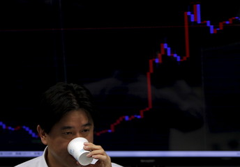 An employee of a foreign exchange trading company holding a paper cup stands in front of a monitor displaying the graph of the recent fluctuations of the exchange rates between the Japanese yen against the U.S. dollar at its dealing room in Tokyo