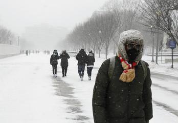 People walk under snow along Pennsylvania Avenue in Washington