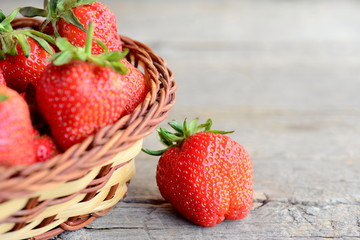 Ripe bright red strawberries fruits. Large juicy strawberries in a wicker basket and on rustic wooden background with copy space for text. Closeup