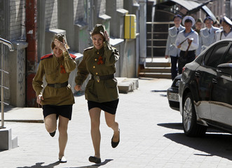 Girls dressed in Red Army uniforms run after taking part in a historic re-enactment in Kiev