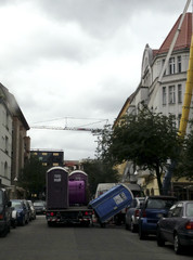 Plastic toilet cabins are loaded on a truck near a construction site in Berlin's Westend
