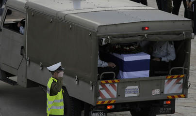 An Israeli soldier salutes as an army vehicle carrying the flag draped coffin of former Israeli Prime Minister Sharon arrives to Latrun