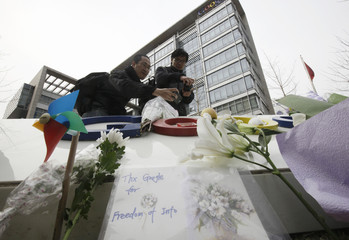 A card and flowers are seen on a platform in front of the Google logo at its China headquarters building in Beijing