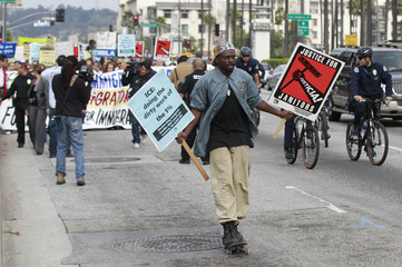 Alonzo Smith rides a skateboard ahead of a group during an Occupy ICE protest march in Los Angeles