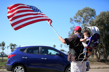 Demonstrator Steven Morales with his son Steven Jr. waves an American flag for motorists in support of President elect Donald Trump outside of Camp Pendleton in Oceanside, California
