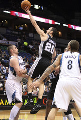 San Antonio Spurs' Ginobili shoots a layup over Minnesota Timberwolves' Love and Beasley during the first half of their NBA basketball game in Minneapolis
