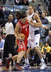 Rockets power forward Scola tries to drive on Mavericks power forward Nowitzki during their NBA basketball game in Dallas, Texas